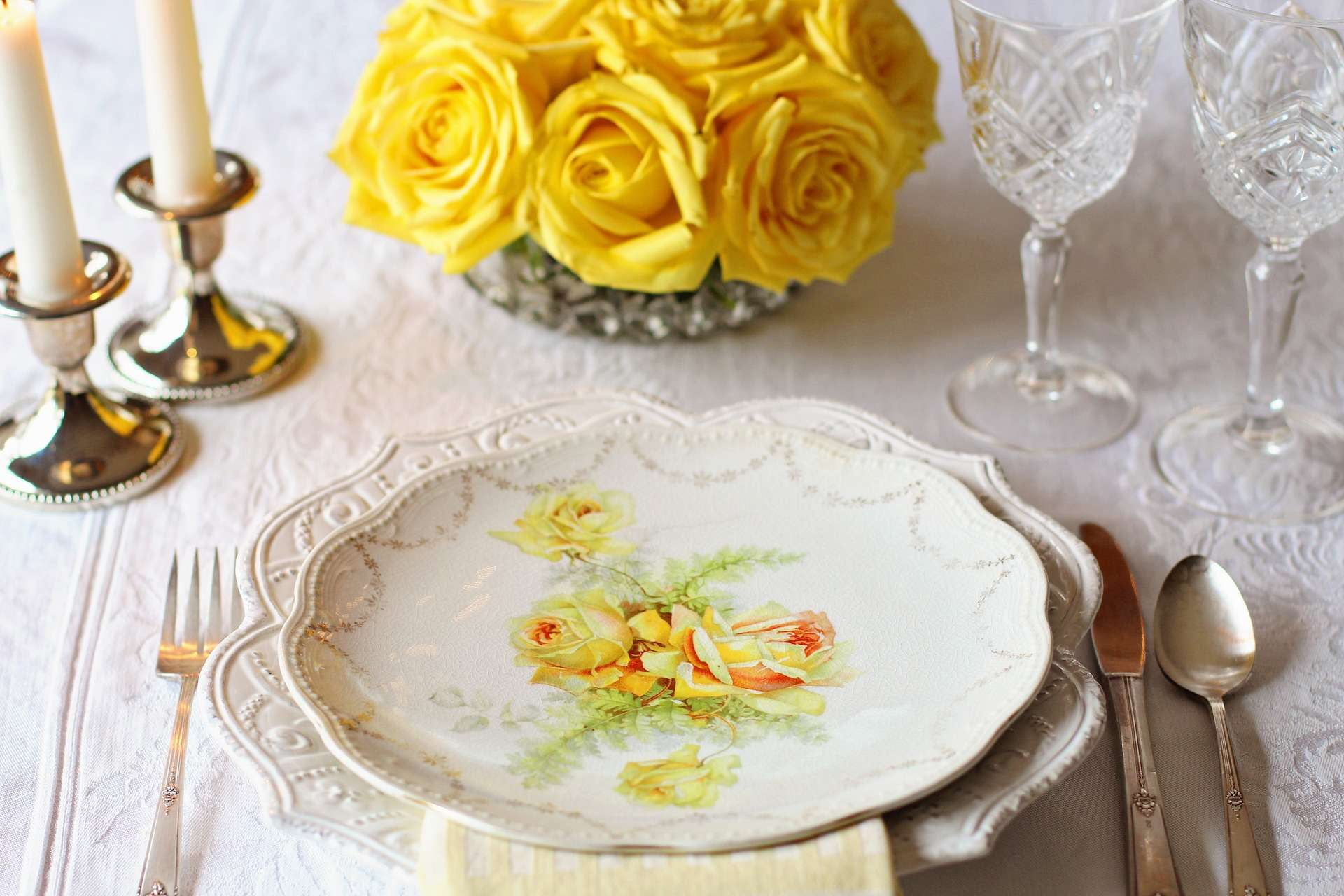 Table Setting Candlesticks Wine glasses, yellow roses to match the yellow rose pattern on the plate.