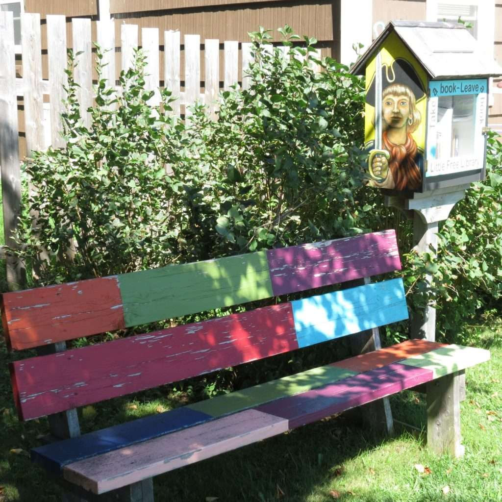 A colourful bench with a Little free Library